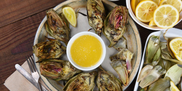 High angle view of a plate full of grilled artichokes with lemons, butter and mayonaise, with a plate for the eaten leaves.